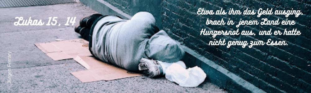 schlafender Mensch vor einer blauen Mauer auf der Straße