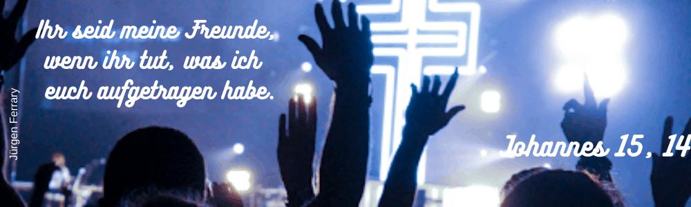 Menschen mit erhobenen Händen vor einer Bühne mit Kreuz