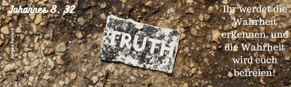 """Auf Kieselsteineen liegt ein Schild """"Truth"""""""