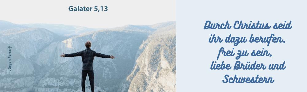 Mann steht auf dem Gipfel und schaut die Berglandschaft an