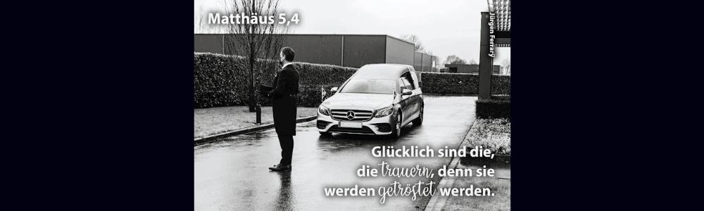 Mann steht auf der Straße vor einem Mercedes