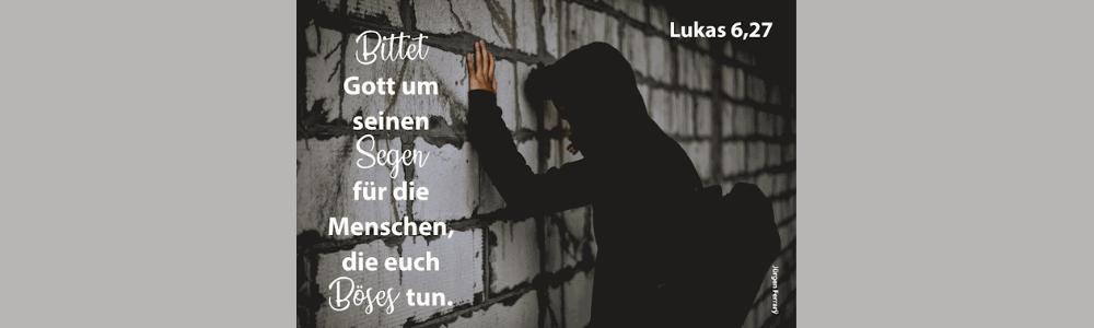 Mann mit schwarzen Kaputzen Pulli lehnt gegen eine  Mauer
