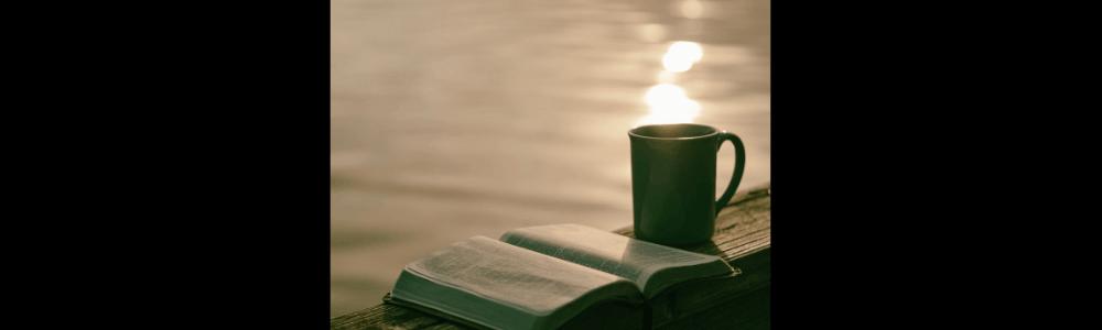 In der Bibel lesen mit einer Tasse Kaffee am Wasser