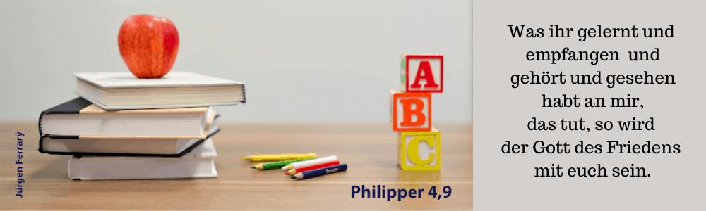 Auf dem Schreibtisch liegen Bücher und ein Apfel mit Buntstiften und ABC-Würfel