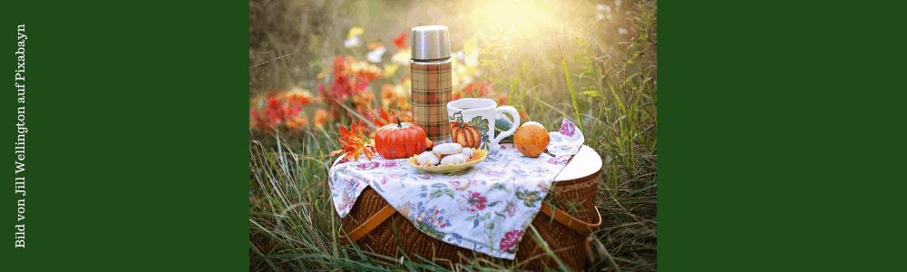 Picknickkorb auf dem Feld mit Essen und Getränken im Sonnenschein