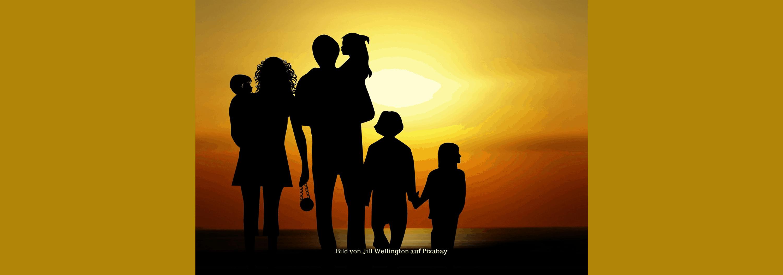 Familie am Wasser beim Sonnenuntergang