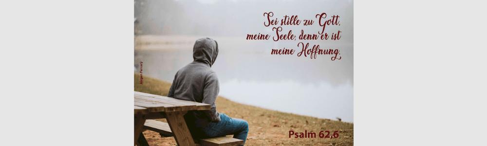 Mann sitzt am See und schaut in die Weite